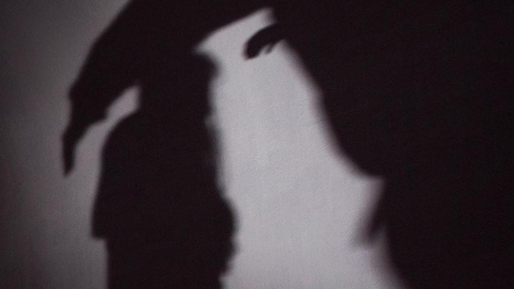 Kvinna överfalls i silhuett. Skylt på våldtäktsmottagning.