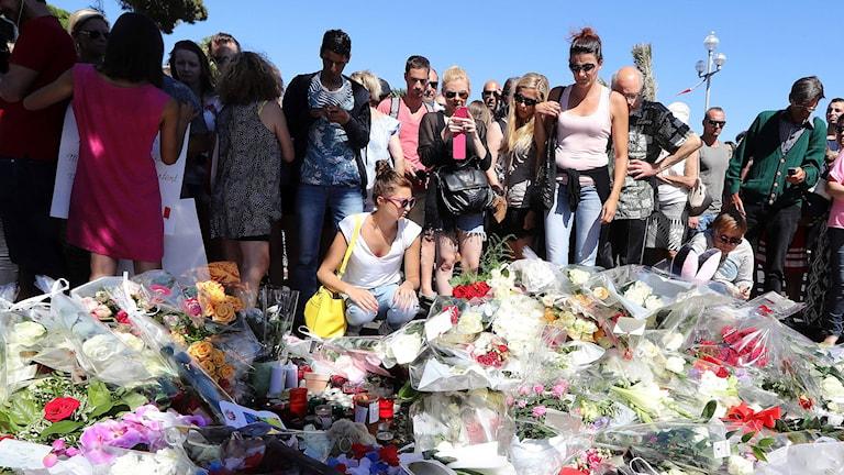 Sörjande lägger blommor på en gata i Nice efter attacken i Nice.