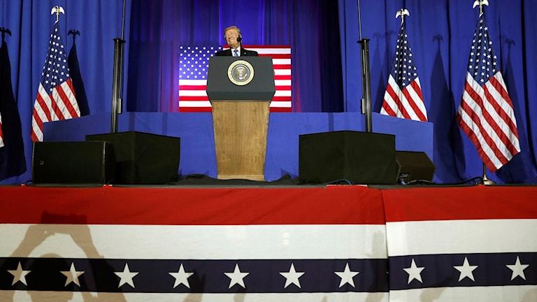 Man i talarstol med flaggor i bakgrund.