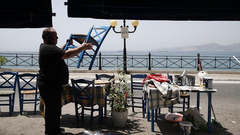 Man ställer ut stolar på en uteservering i Grekland inför att landet ska öppna för turister igen.