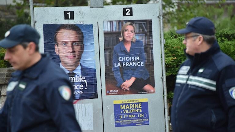 Poliser går förbi valaffischer med Le Pen och Macron.