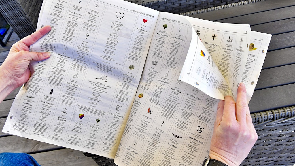 En person läser dödsannonserna i en dagstidning.