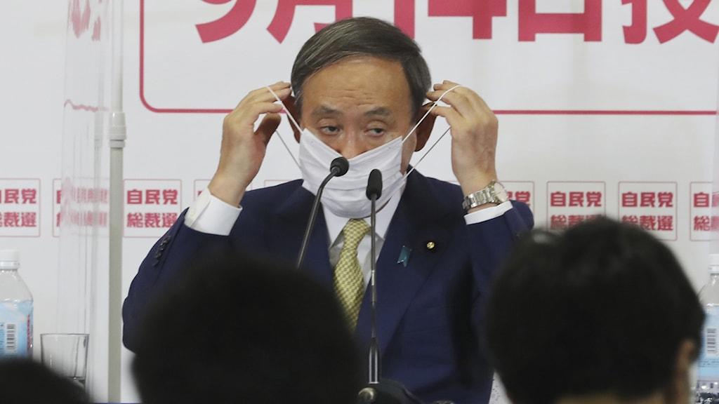 Man som tar av sig sitt munskydd.