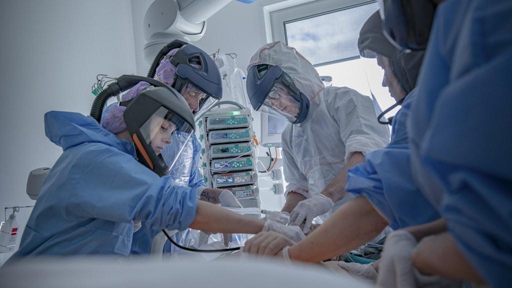 Personal med skyddsutrustning arbetar med en patient. Foto: Staffan Löwstedt/SvD/TT