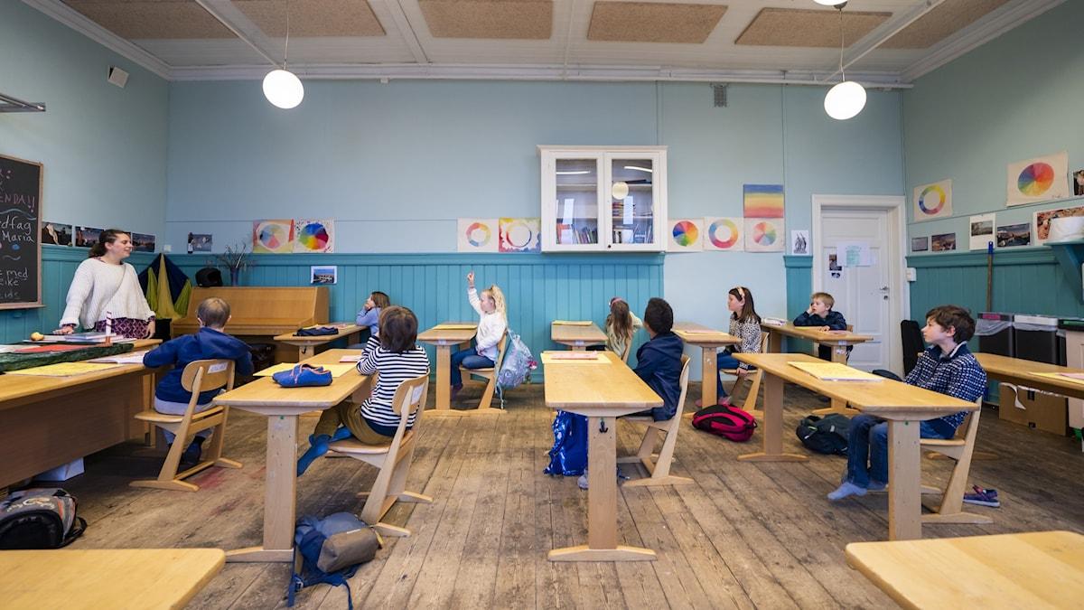 På bilden syns ett klassrum med en lärare och flera elever.
