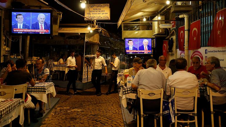 Folk sitter vid bord framför TV-apparater som visar debatten mellan borgmästarkandidaterna i Istanbul