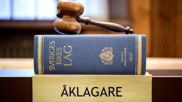 """Lagbok ovanpå skylt med texten """"Åklagare""""."""