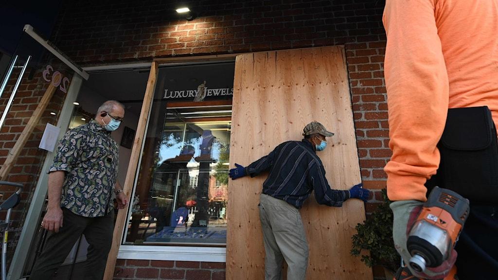 tre män sätter upp plywood för butiksfönster