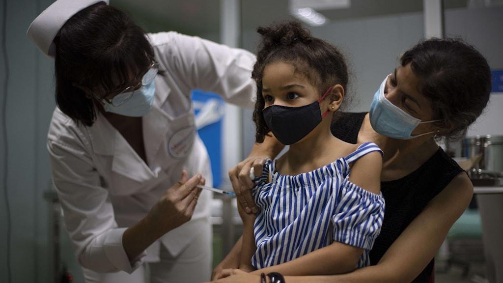 Liten flicka får en vaccinspruta.