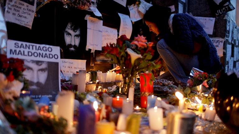Många tända ljus och bilder på Santiago Maldonado. En kvinna tänder ljus.
