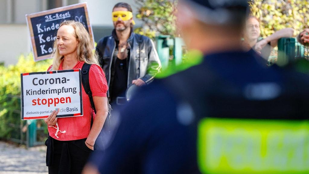 En blond kvinna med röd tröja och en man med gul mask över ögonen håller upp plakat mot vaccination. Polis i förgrund.