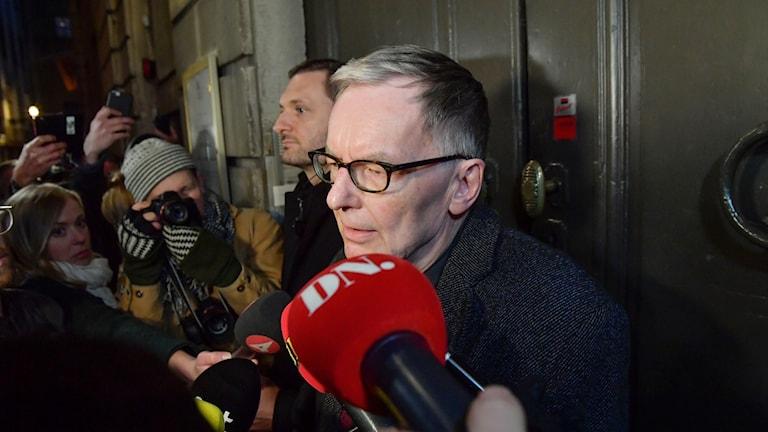 Akademiledamoten Anders Olsson ger kommentarer till journalisterna då han lämnar Börshuset i Gamla stan efter Svenska Akademiens sammanträde på torsdagen.