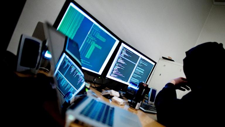 En man framför flera datorer.