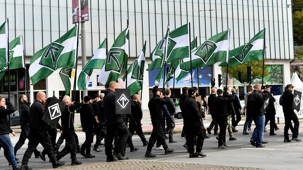 Svartklädda män går med grönvita flaggor.