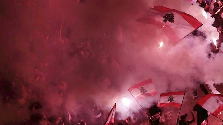 Demonstration med rödfärgad rök och libanesiska flaggor.