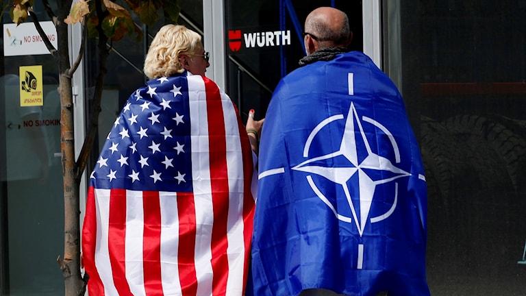 Två människor med en amerikansk och en natoflagga på ryggarna.