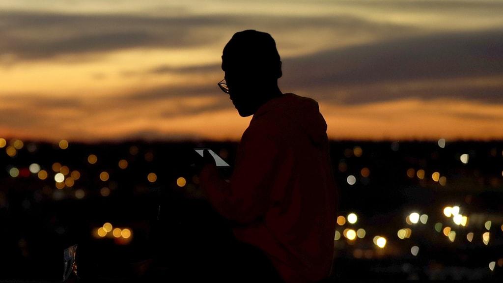 Kvinna tittar på telefon i mörker