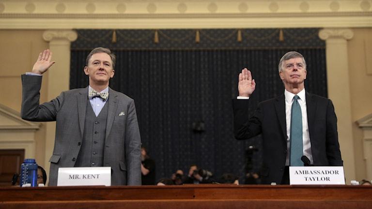 två män håller upp handen i rättssal.