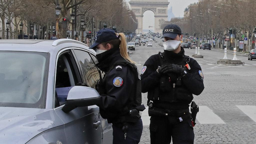 Fransk polis kontrollerar förbipasserande i Paris. Personer som saknar intyg om var de är på väg riskerar att bötfällas.