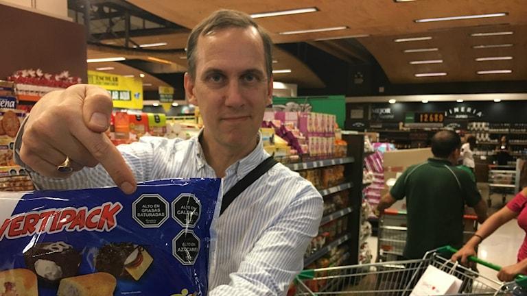 Globala hälsokorrespondenten Johan Bergendorff visar upp förpackning med varning mot fett kalorier och socker i snabbköp i Chile.