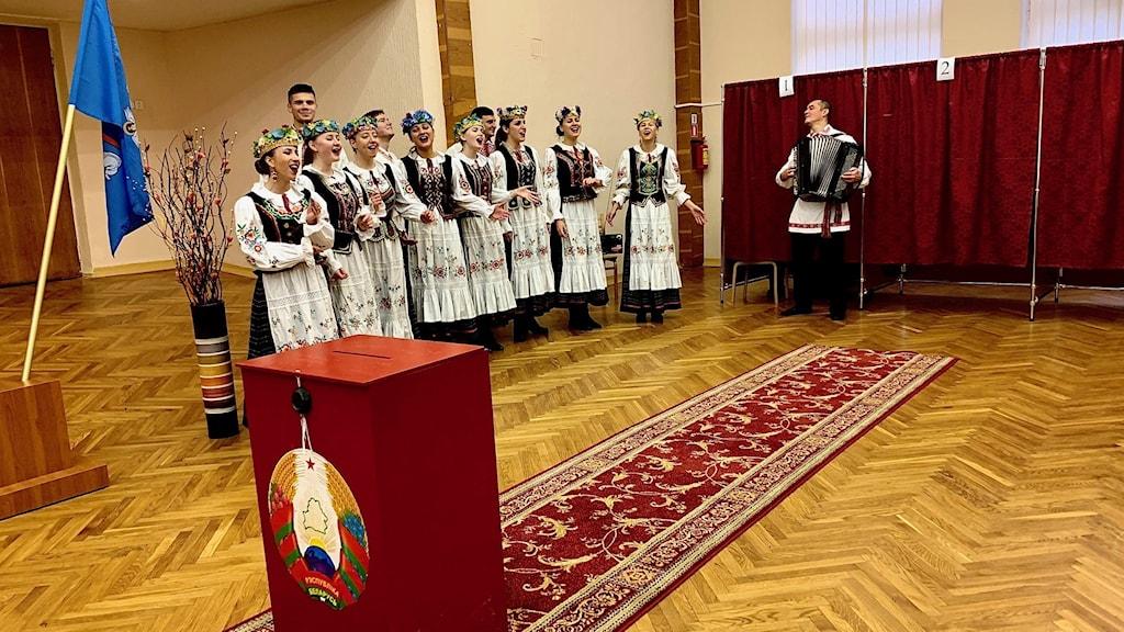 Iklädda färgglada folkdräkter sjunger universitetets folksångsensemble och det blir även lite dans på vallokalens trägolv.