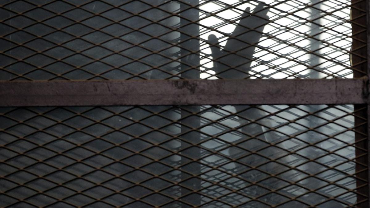 En man vinkar inifrån en cell i ett egyptiskt fängelse.