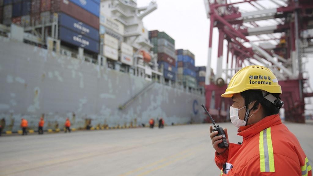 Hamnarbetare med walkie talkie, fartyg i bakgrunden.