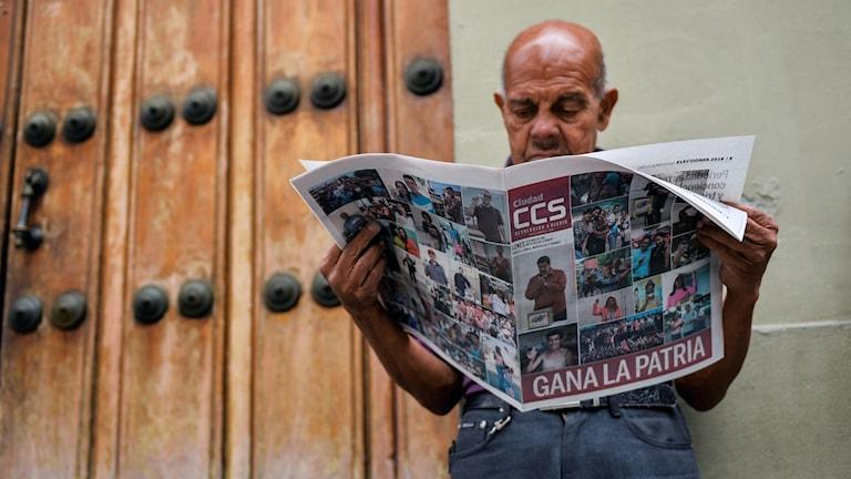 En man i Venezuela läser om valresultatet i tidningen.