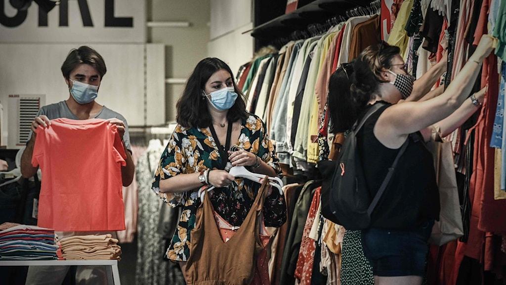 Personer i en klädaffär med munskydd.