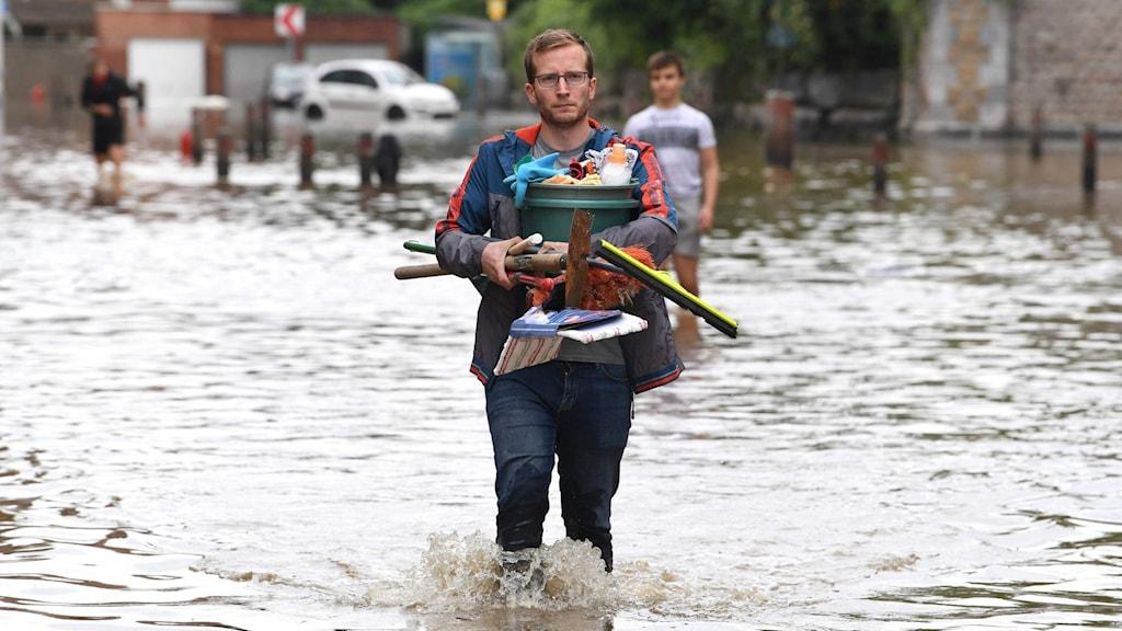 Man som vadar i vatten med famnen full av ägodelar.