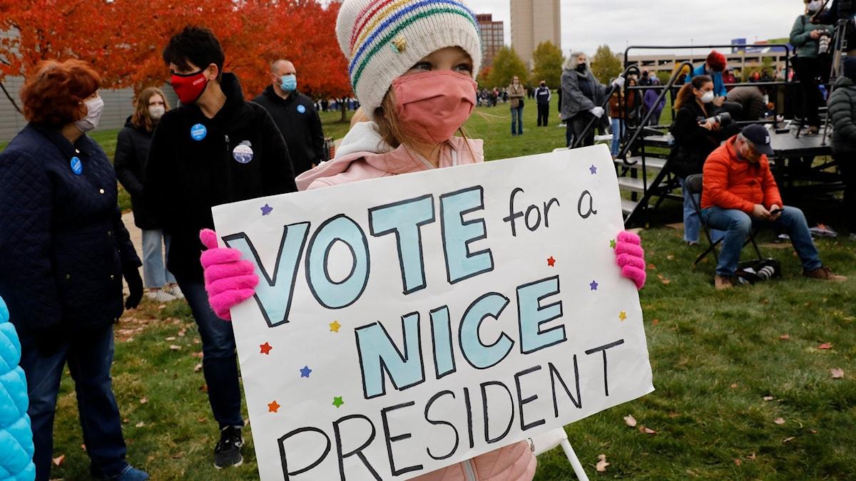 """Liten flicka med plakat med texten """"Rösta för en snäll president"""""""