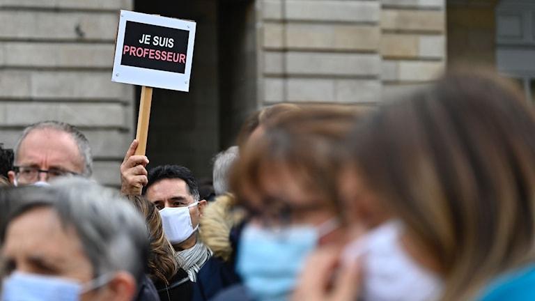 """Tusentals fransmän har i dag tagit till gatorna för att hedra den mördade läraren. Många bär skyltar med budskapet """"Je suis professeur"""" – """"Jag är lärare."""""""