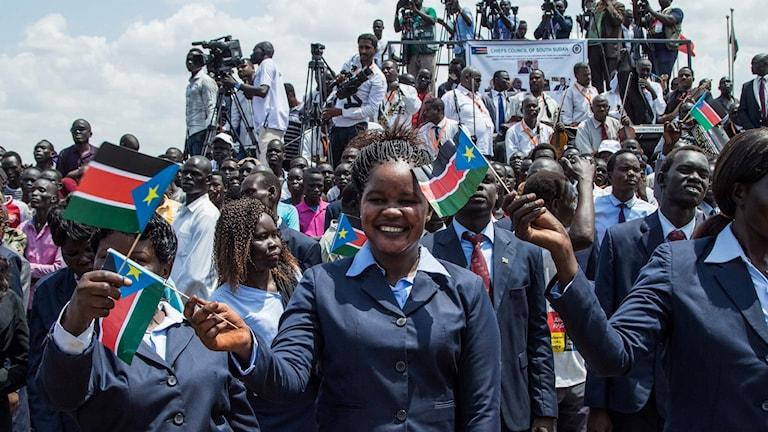 Människor viftar med Sydsudans flagga under en fredsceremoni i Juba i Sydsudan.