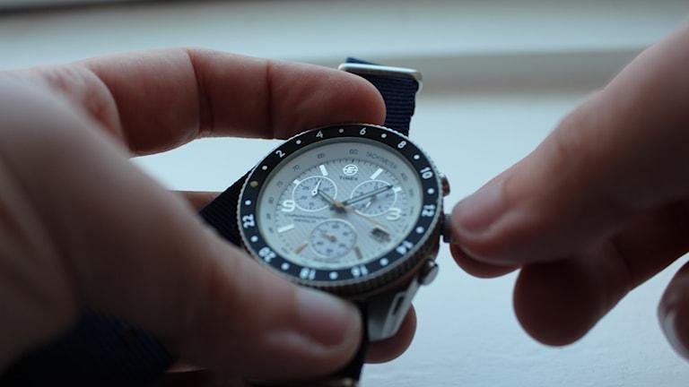 Person ställer om klocka.