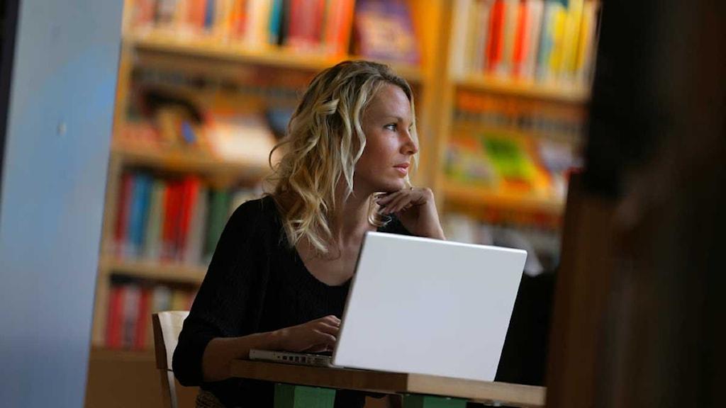 Ung kvinna sitter vid sin laptop i ett bibliotek. Foto: Foto: Fredrik Sandberg / Scanpix