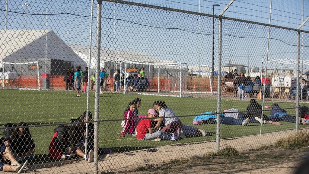 Bilden visar tonåringar, bakom ett stängsel i tältläger i Tornillo, Texas, USA. Överst på stängslet syns taggtråd. Barnen sitter på en fotbollsplan. Foto: Ivan Pierre Aguirre/AP/TT