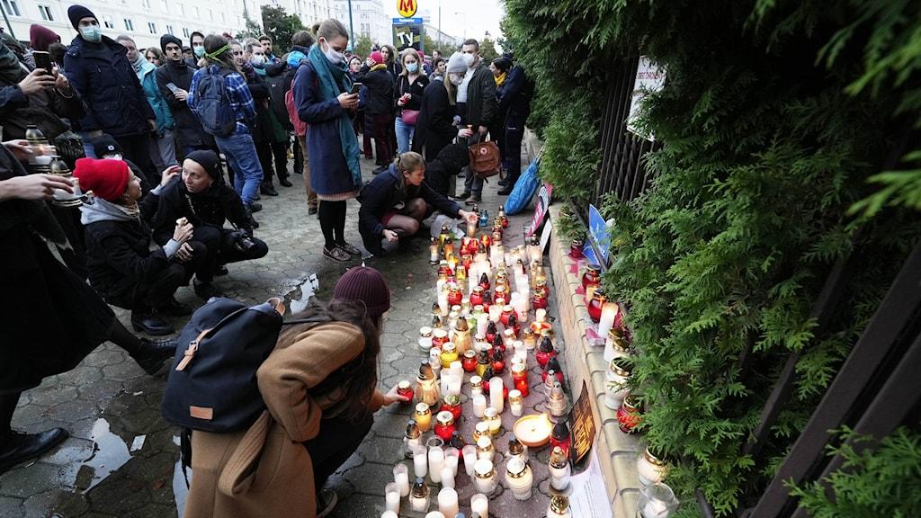 Utanför polska gränsbevakningens högkvarter tänder Warszawabor ljus för de migranter som dött på gränsen mellan Polen och Belarus.