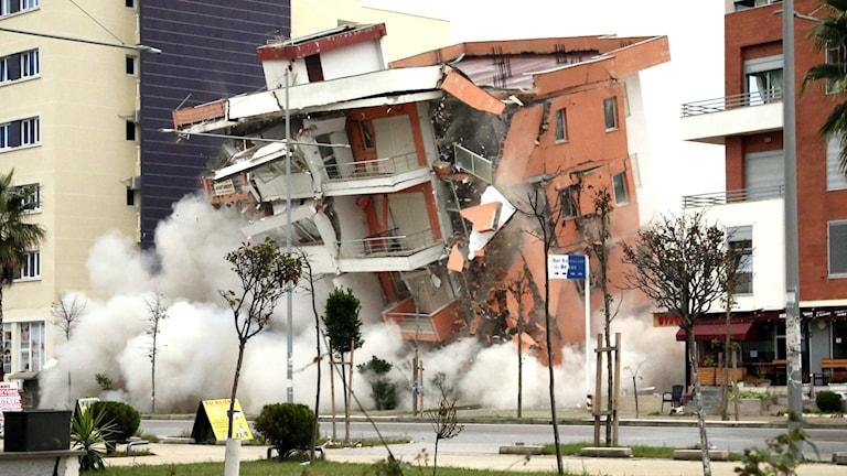 Hus som faller under jordbävning.