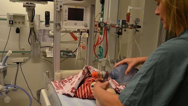 Läkare som övar med barndocka