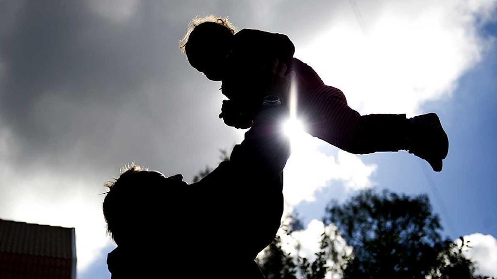 Vuxen svingar barn i luften. Foto: Jessica Gow/Scanpix.