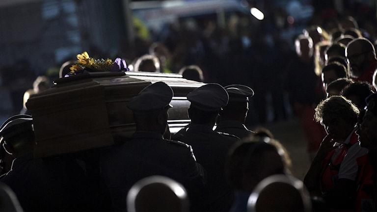 En av kistorna bärs bort vid begravningen i Amatrice i dag.