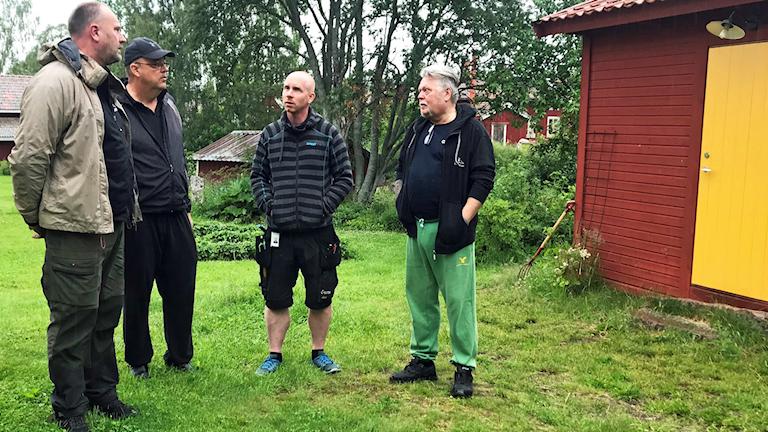 Fyra män står ute och pratar.