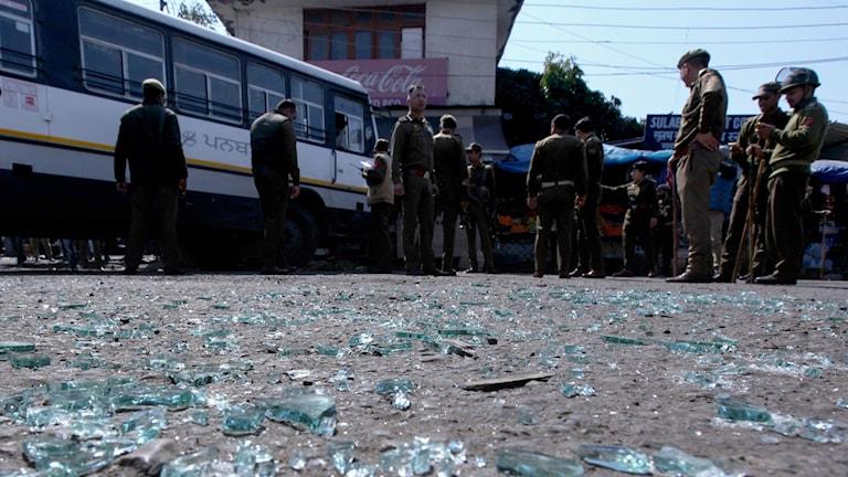 Indisk polis kontrollerar en buss efter en granatattack.