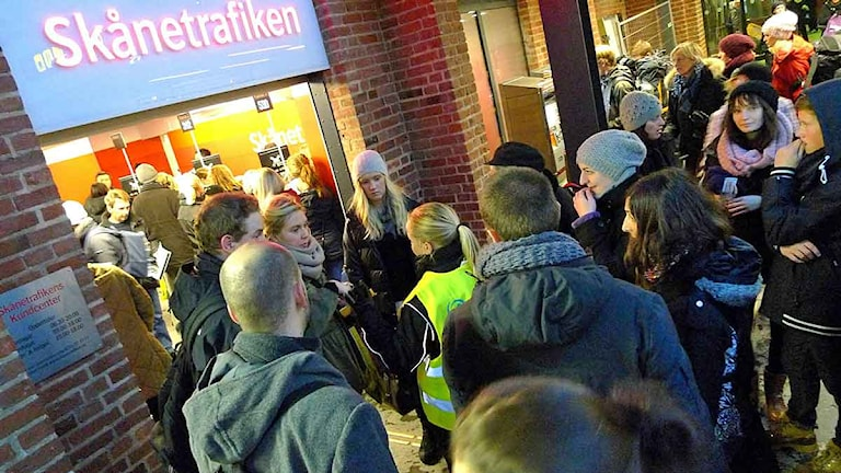 Personer väntar under en skylt där det står Skånetrafiken. Foto: Johan Nilsson/TT.