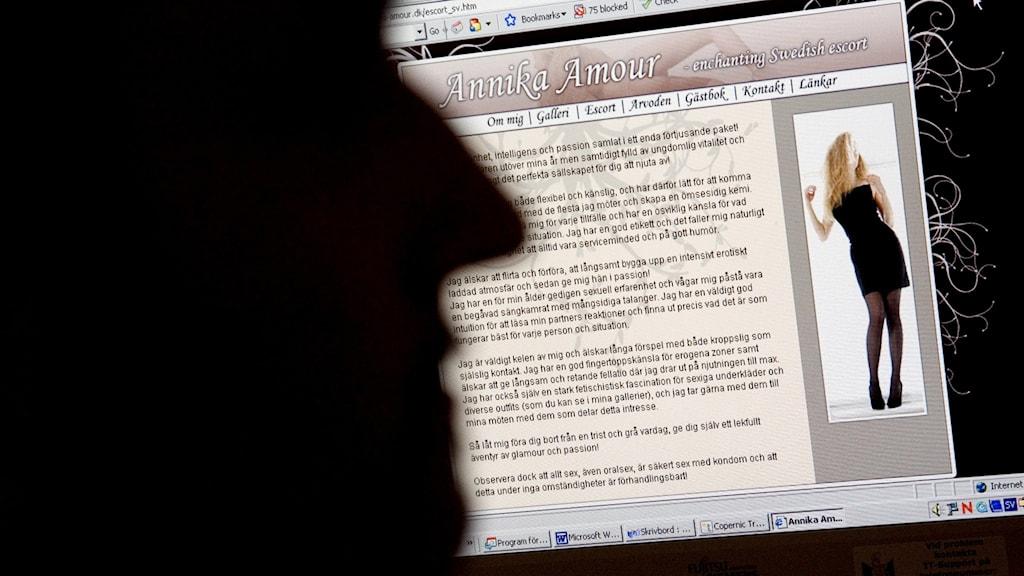 Profilen av en man framför en sexköpssajt med annons och bild av kvinna på datorskärm.