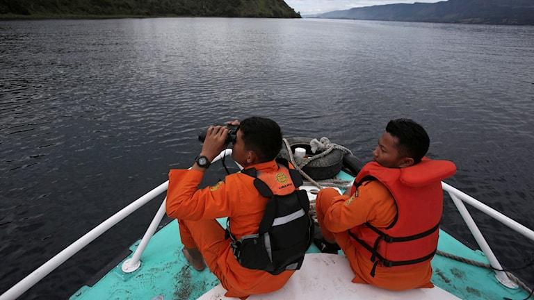 Räddningsteam söker av horisonten med en kikare ombord på en räddningsbåt i hopp om att hitta personer som saknas etfer färjeolyckan.