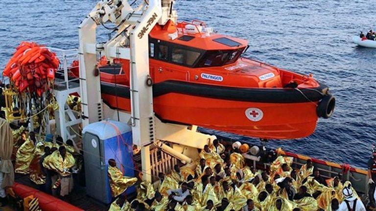 räddningsbåt med många räddade människor insvepta i foliefiltar