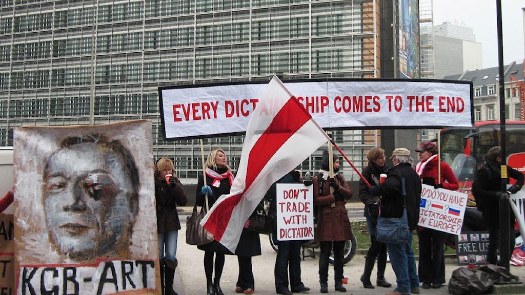 """Demonstration för EU-sanktioner mot Vitryssland inför utrikesministermötet i Bryssel. """"KGB-konst"""", står det på den målade bilden av ett blåslaget ansikte. Foto: Jens Möller/Sveriges Radio."""