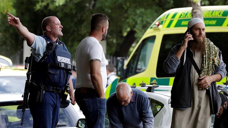 Polis försöker få bort människor från gatan utanför moskén i Christchurch.