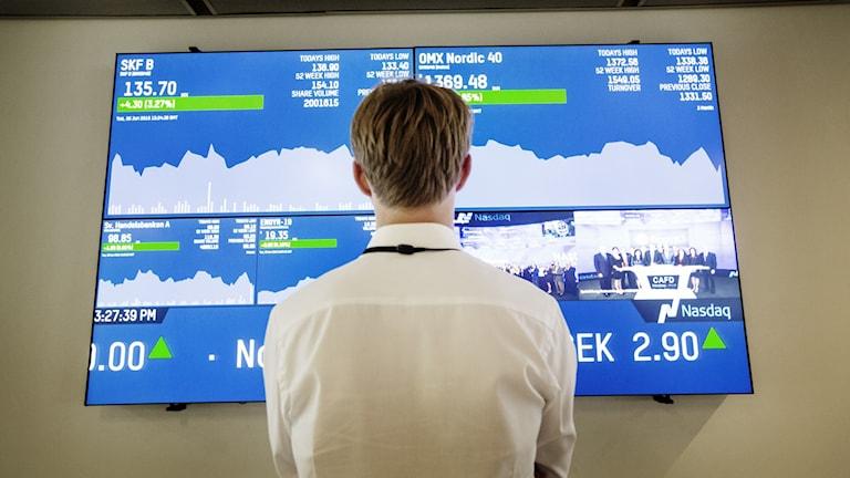 Arkivbild på man som står framför en skärm med börskurvor.